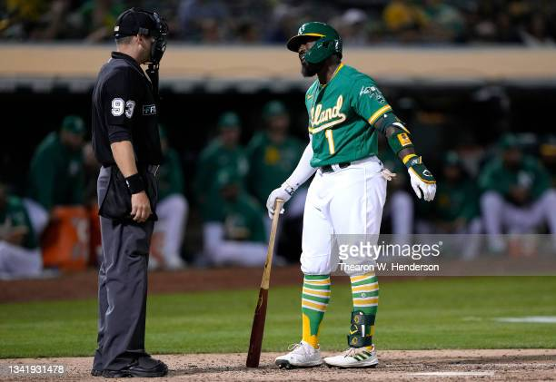 Josh Harrison of the Oakland Athletics argues with home plate umpire Will Little after Harrison was called out on strike against the Seattle Mariners...