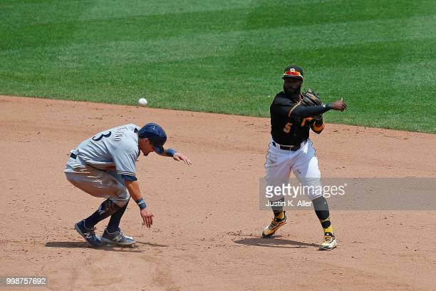 Josh Harrison of the Pittsburgh Pirates attempts to turn a double play in the fifth inning during game one of a doubleheader against Tyler Saladino...