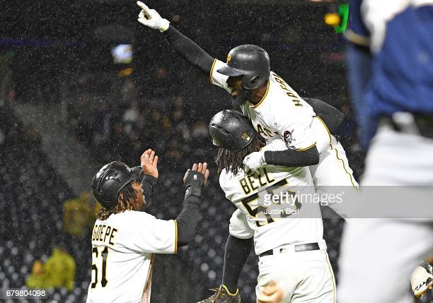 Josh Harrison of the Pittsburgh Pirates celebrates with Josh Bell and Gift Ngoepe after hitting a walk off single giving the Pittsburgh Pirates a 21...