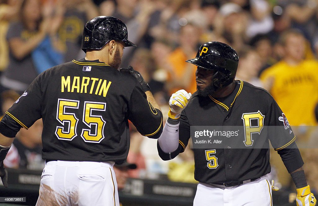 Josh Harrison #5 of the Pittsburgh Pirates celebrates with Russell Martin #55 after scoring on a sacrifice fly in the seventh inning against the Washington Nationals during the game at PNC Park May 24, 2014 in Pittsburgh, Pennsylvania.