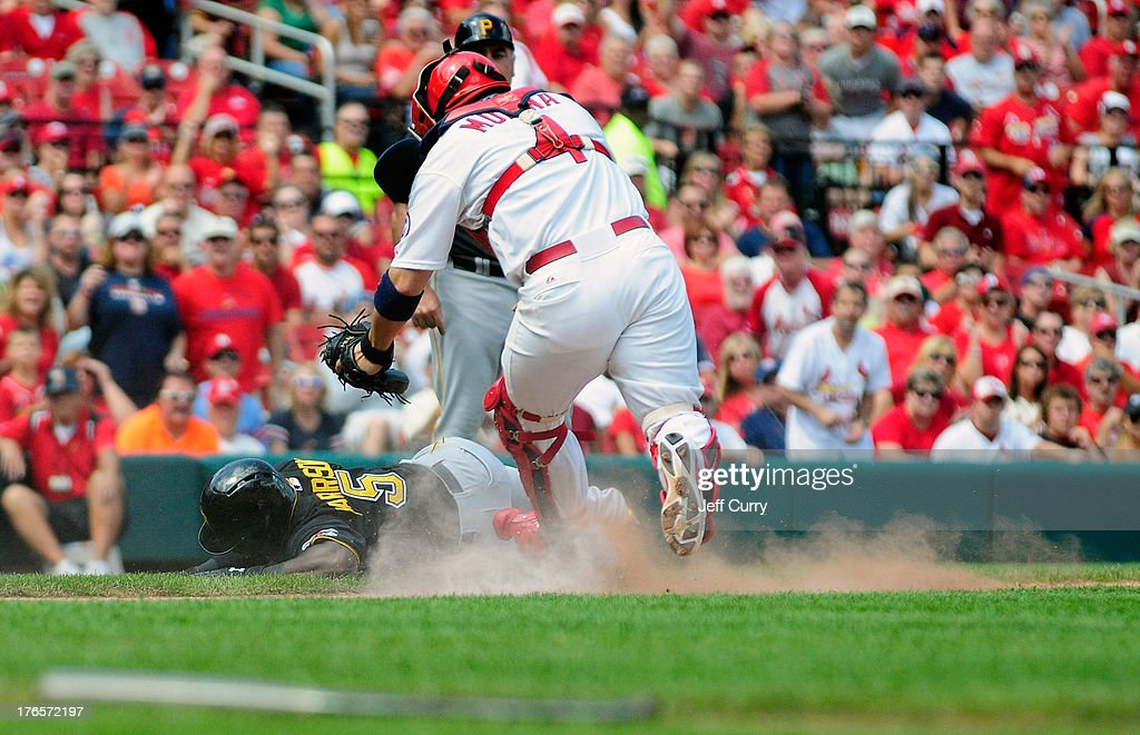 Josh Harrison #5 of the Pittsburgh Pirates falls being tagged out by catcher Yadier Molina #4 of the St. Louis Cardinals during the seventh inning at Busch Stadium on August 15, 2013 in St. Louis, Missouri. Cardinals won 6-5 in twelve innings.