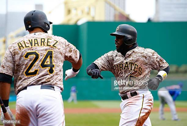 Josh Harrison of the Pittsburgh Pirates is congratulated by teammate Pedro Alvarez after scoring the goahead run in the seventh inning against the...