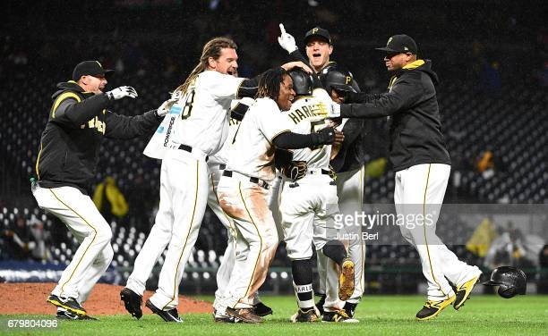 Josh Harrison of the Pittsburgh Pirates is mobbed by teammates after hitting a walk off single giving the Pittsburgh Pirates a 21 win over the...