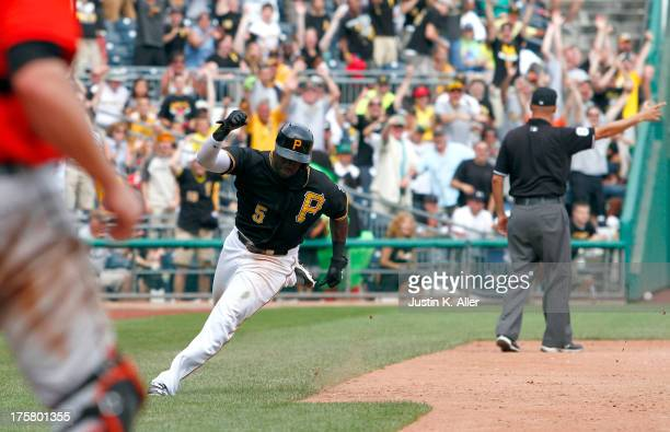 Josh Harrison of the Pittsburgh Pirates scores on a gamewinning RBI single in the tenth inning against the Miami Marlins during the game on August 8...