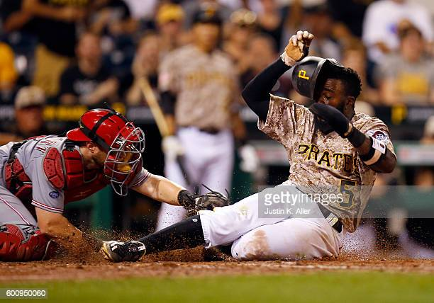 Josh Harrison of the Pittsburgh Pirates scores on a single in the sixth inning against Tucker Barnhart of the Cincinnati Reds during the game at PNC...