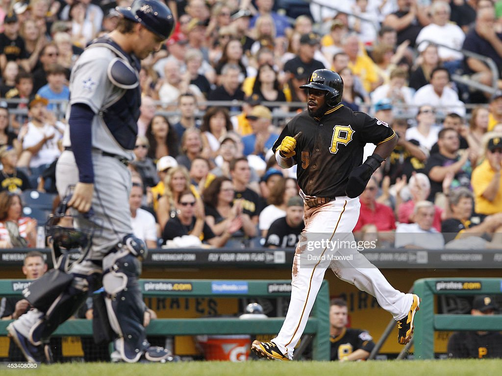 Josh Harrison #5 of the Pittsburgh Pirates scores on an RBI single by Russell Martin #55 (not pictured) as Yasmani Grandal #8 of the San Diego Padres looks on during the first inning of their game on August 9, 2014 at PNC Park in Pittsburgh, Pennsylvania.