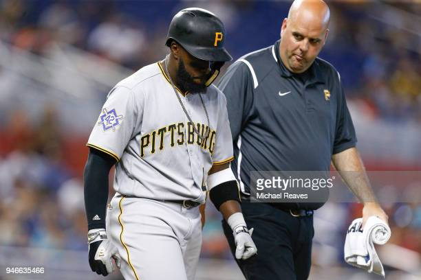 Josh Harrison of the Pittsburgh Pirates walks with a trainer after being hit by a pitch against the Miami Marlins at Marlins Park on April 15 2018 in...