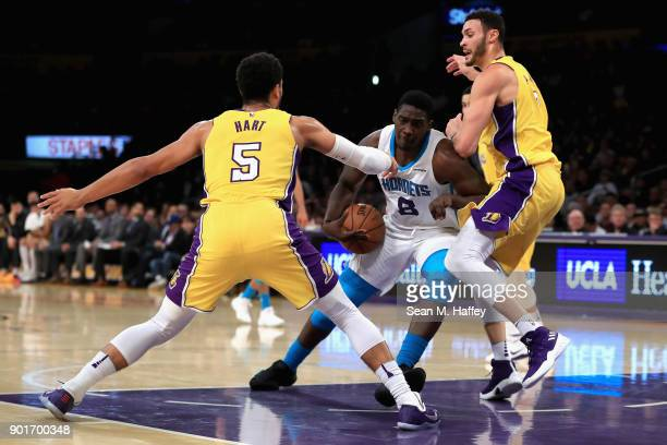 Josh Hart and Larry Nance Jr #7 of the Los Angeles Lakers defend against Johnny O'Bryant III of the Charlotte Hornets during the first half of a game...