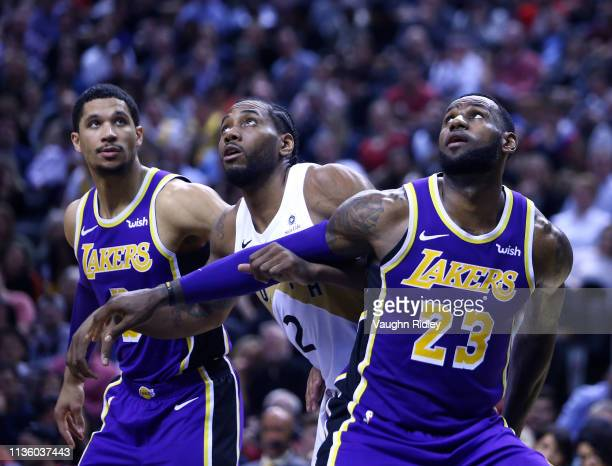 Josh Hart and LeBron James of the Los Angeles Lakers battle with Kawhi Leonard of the Toronto Raptors for a rebound during the second half of an NBA...