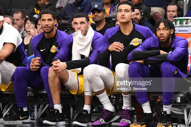 Josh Hart Lonzo Ball Kyle Kuzma and Brandon Ingram of the Los Angeles Lakers look on from the bench during a preseason game against the Golden State...