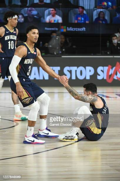 Josh Hart of the New Orleans Pelicans helps up JJ Redick of the New Orleans Pelicans during the game against the Utah Jazz during a game on July 30...