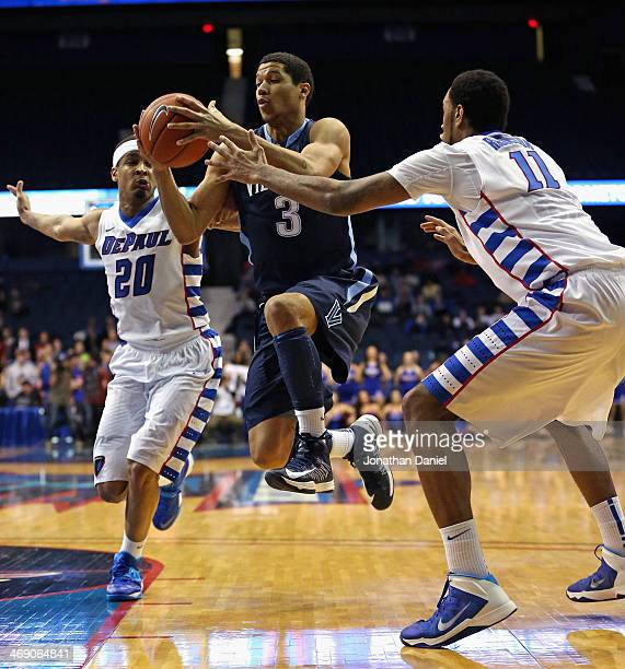 Josh Hart of the Villanova Wildcats drives between Brandon Young and Forrest Robinson of the DePaul Blue Demons at the Allstate Arena on February 12...