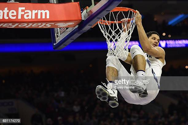 Josh Hart of the Villanova Wildcats gets the dunk against the Marquette Golden Eagles but picks up a violation for hanging on the rim too long during...