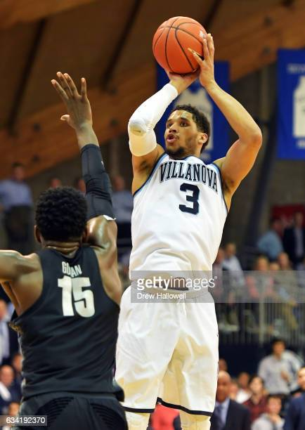 Josh Hart of the Villanova Wildcats shoots and scores a threepointer late in the game over Jessie Govan of the Georgetown Hoyas at The Pavilion on...