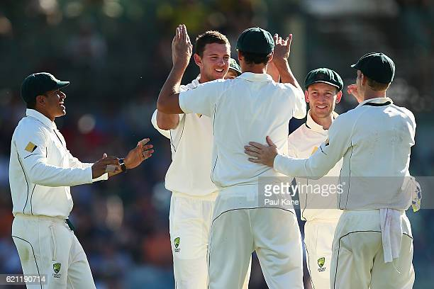 Josh Hazlewood and Mitchell Starc of Australia celebrates the wicket of Dean Elgar of South Africa during day three of the First Test match between...