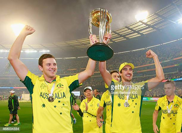 Josh Hazlewood and Mitchell Starc of Australia hold the World Cup trophy aloft as they celebrate after Australia won the 2015 ICC Cricket World Cup...