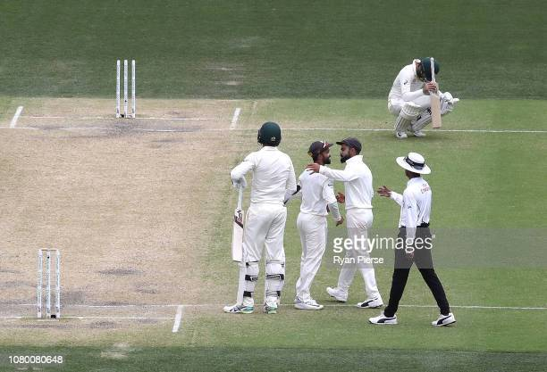 Josh Hazlewood and Nathan Lyon of Australia look dejected as Virat Kohli and Ajinkya Rahane of India celebrate after India claimed victory during day...