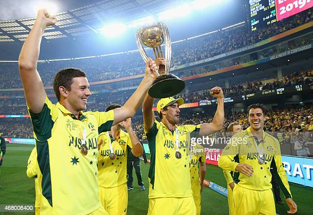 Josh Hazlewood, Mitchell Starc and Pat Cummins of Australia celebrates with the trophy during the 2015 ICC Cricket World Cup final match between...