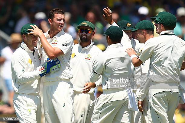 Josh Hazlewood of Australia celebrates with Peter Nevill after dismissing Dean Elgar of South Africa during day one of the First Test match between...