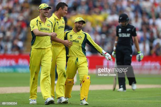 Josh Hazlewood of Australia is congratulated by Pat Cummins and wicketkeeper Matthew Wade after capturing his fifth wicket during the ICC Champions...