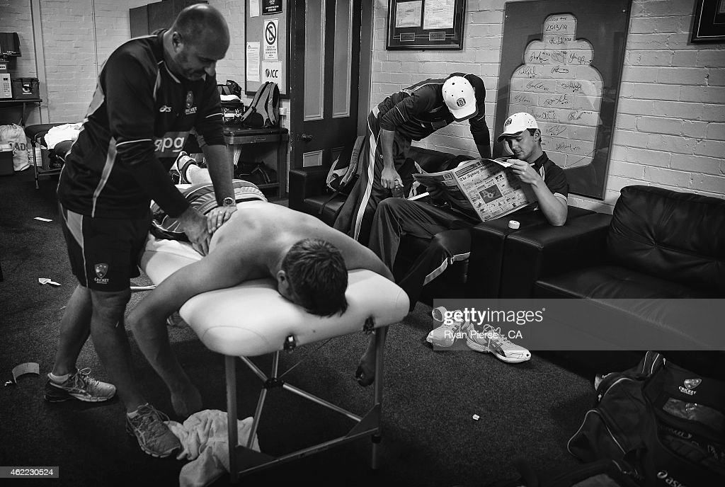 Josh Hazlewood of Australia reads the paper as Alex Kountouris, Australian Team Physiotherapist, massages James Faulkner of Australia during a rain delay during the One Day International match between Australia and India at Sydney Cricket Ground on January 26, 2015 in Sydney, Australia.