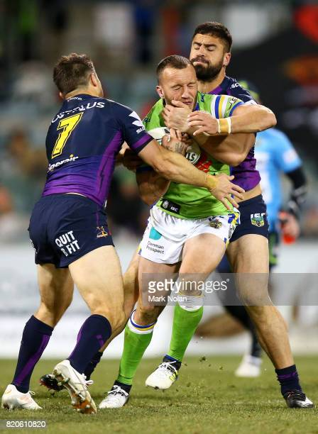Josh Hodgson of the Raiders is tackled during the round 20 NRL match between the Canberra Raiders and the Melbourne Storm at GIO Stadium on July 22...