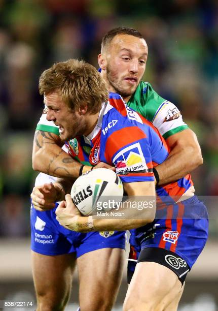 Josh Hodgson of the Raiders tackles Nathan Ross of the Knights during the round 25 NRL match between the Canberra Raiders and the Newcastle Knights...
