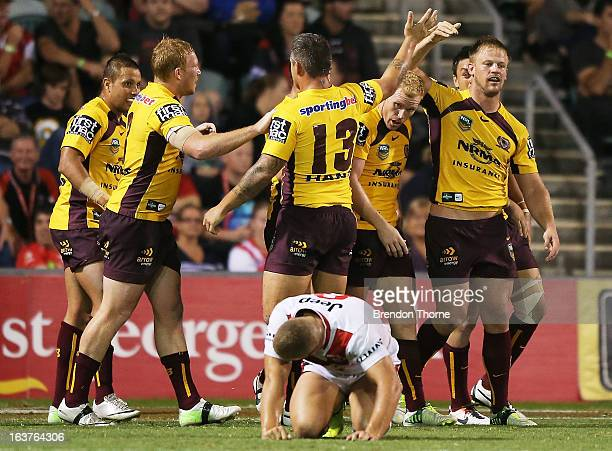 Josh Hoffman of the Broncos celebrates with team mates after scoring during the round two NRL match between the St George Dragons and the Brisbane...
