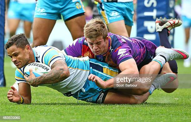 Josh Hoffman of the Gold Coast Titans is tackled by Christian Welch of the Melbourne Storm during the round 22 NRL match between the Melbourne Storm...
