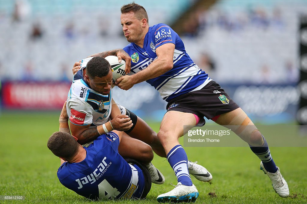 Josh Hoffman of the Titans is tackled by Josh Reynolds and Kerrod Holland of the Bulldogs during the round eight NRL match between the Canterbury Bulldogs and the Gold Coast Titans at ANZ Stadium on April 23, 2016 in Sydney, Australia.