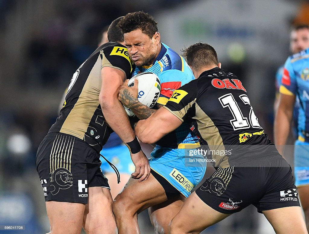 Josh Hoffman of the Titans is tackled by Reagan Campbell-Gillard and James Fisher-Harris of the Panthers during the round 25 NRL match between the Gold Coast Titans and the Penrith Panthers at Cbus Super Stadium on August 27, 2016 in Gold Coast, Australia.