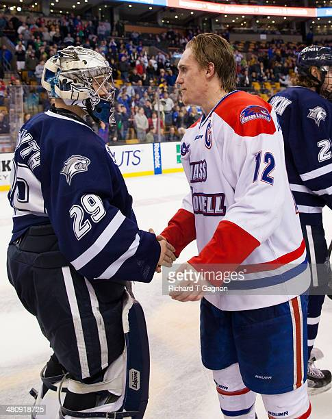 Josh Holmstrom of the Massachusetts Lowell River Hawks shakes hands with Casey DeSmith of the New Hampshire Wildcats after NCAA hockey action in the...