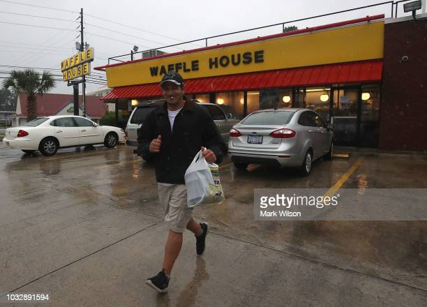 Josh Honeycutt runs to his car after picking up food at Waffle House as the effects of Hurricane Florence start to hit the area on September 13 2018...