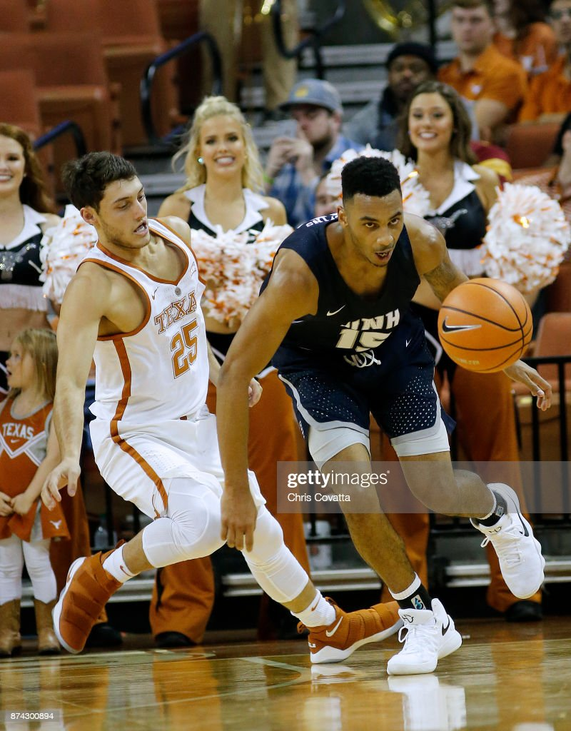 Josh Hopkins #15 of the New Hampshire Wildcats drives with the ball against Joe Schwartz #25 of the Texas Longhorns at the Frank Erwin Center on November 14, 2017 in Austin, Texas.