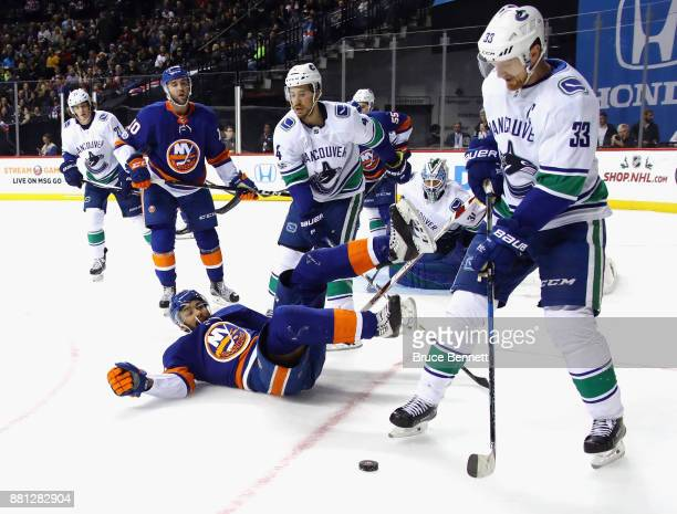 Josh HoSang of the New York Islanders is tripped up by Michael Del Zotto of the Vancouver Canucks during the second period at the Barclays Center on...