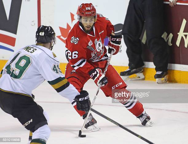 Josh HoSang of the Niagara IceDogs controls the puck in front of a checking Max Jones of the London Knights during Game Four of the OHL Championship...