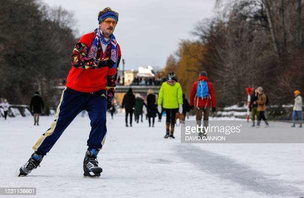 Josh ice-skates on the frozen Landwehr Canal in Berlin's Kreuzberg district on February 13, 2021 as hundreds of people ignored the warnings not to go...