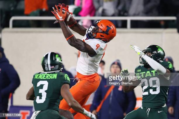 Josh Imatorbhebhe of the Illinois Fighting Illini catches a fourth quarter fourth down pass to keep the drive alive between Xavier Henderson and...