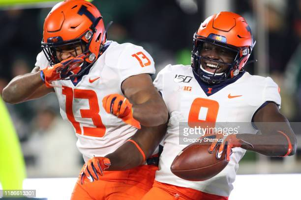Josh Imatorbhebhe of the Illinois Fighting Illini celebrates his fourth quarter touchdown with Caleb Reams while playing the Michigan State Spartans...