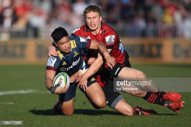 Josh Ioane of the Highlanders is tackled by Jack Goodhue of the Crusaders during the round 9 Super Rugby Aotearoa match between the Crusaders and the...