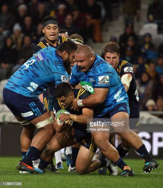 Josh Ioane of the Highlanders is wrapped up by Karl Tu'inukuafe of the Blues during the round 10 Super Rugby match between the Highlanders and the...