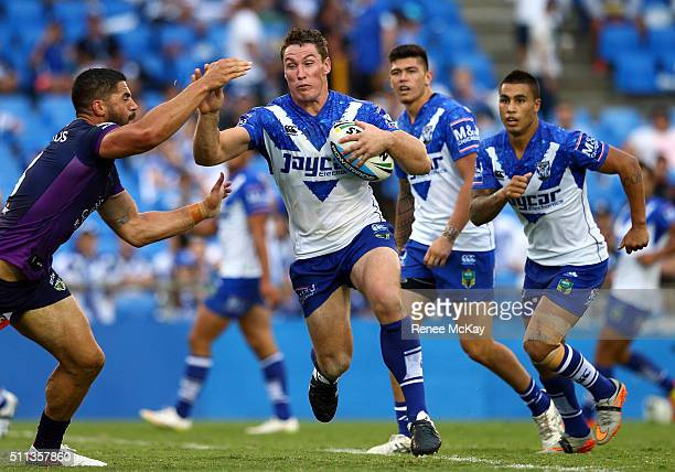 Josh Jackson of the Bulldogs fends off the tackle of Jesse Bromwich of the Storm during the NRL Trial match between the Canterbury Bulldogs and the...