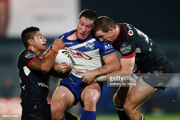 Josh Jackson of the Bulldogs is tackled by Ata Hingano and Ryan Hoffman of the Warriors during the round 16 NRL match between the New Zealand...