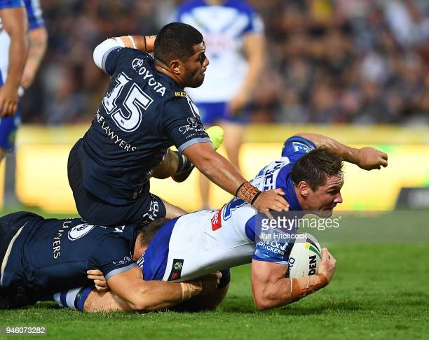Josh Jackson of the Bulldogs is tackled by John Asiata of the Cowboys during the round six NRL match between the North Queensland Cowboys and the...