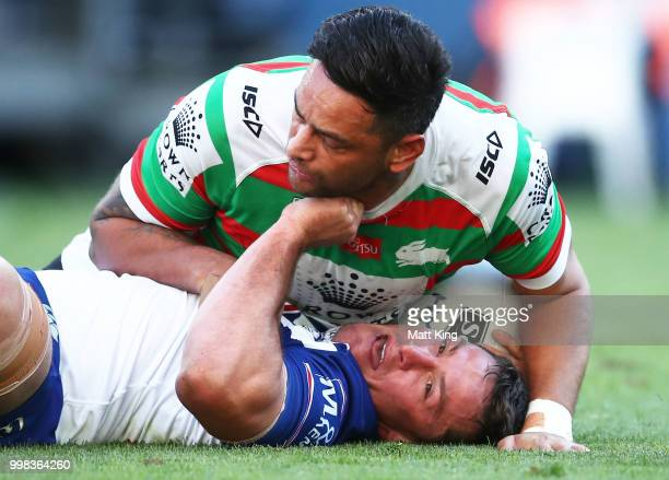 Josh Jackson of the Bulldogs is tackled by John Sutton of the Rabbitohs during the round 18 NRL match between the Canterbury Bulldogs and the South...