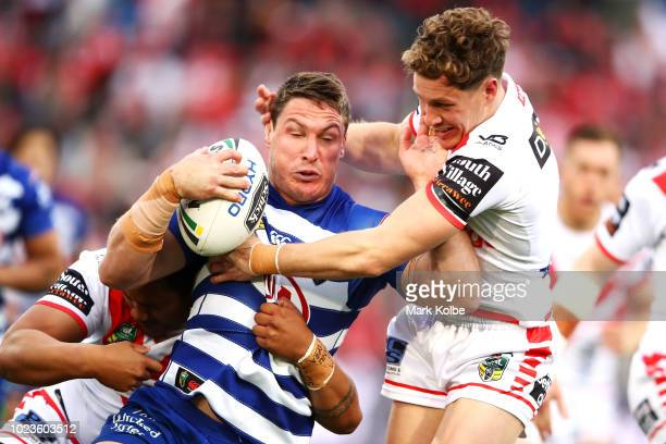 Josh Jackson of the Bulldogs is tackled by Kurt Mann of the Dragons during the round 24 NRL match between the St George Illawarra Dragons and the...
