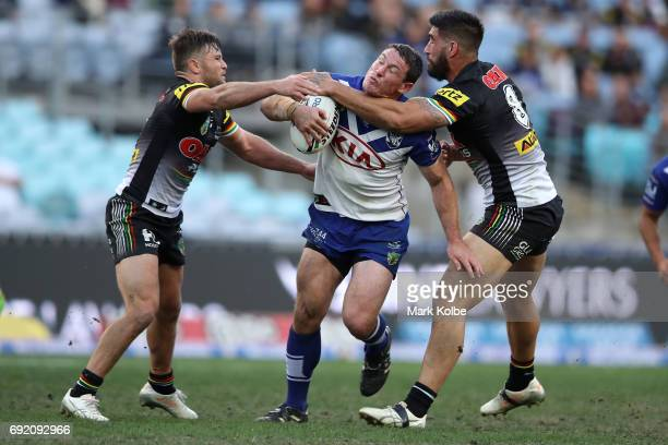 Josh Jackson of the Bulldogs is tackled by Mitch Rein and James Tamou of the Panthers during the round 13 NRL match between the Canterbury Bulldogs...