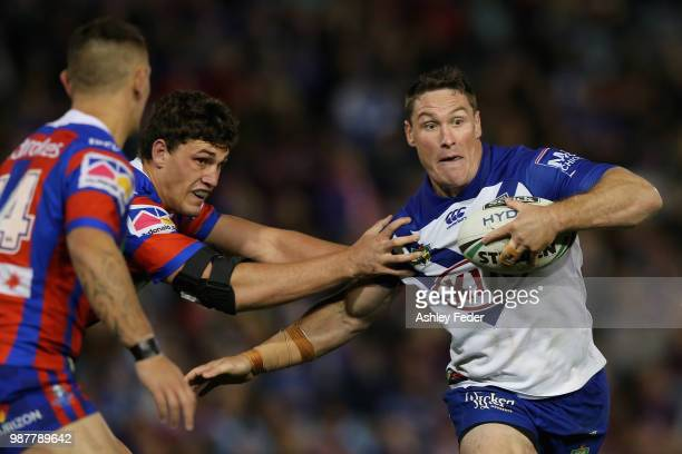Josh Jackson of the Bulldogs is tackled by the Knights defence during the round 16 NRL match between the Newcastle Knights and the Canterbury...
