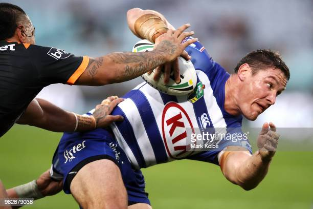 Josh Jackson of the Bulldogs is tackled during the round 12 NRL match between the Wests Tigers and the Canterbury Bulldogs at ANZ Stadium on May 27...