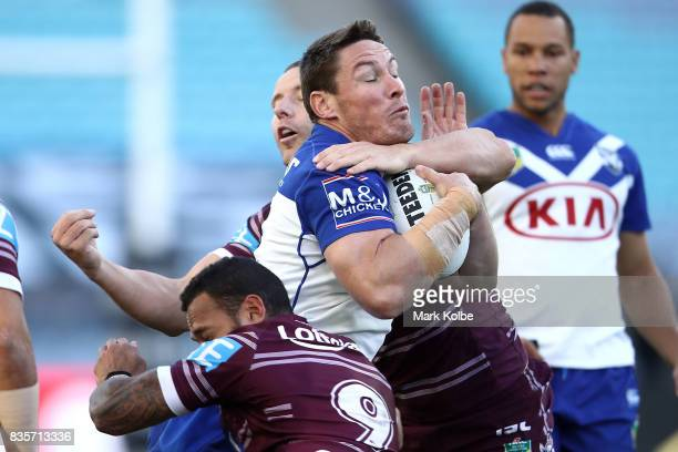 Josh Jackson of the Bulldogs is tackled during the round 24 NRL match between the Canterbury Bulldogs and the Manly Sea Eagles at ANZ Stadium on...